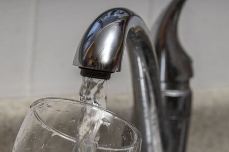 Glass at water tap and filling water with lead contamination Banque d'images