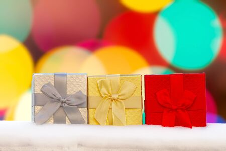 Colourful Gif boxes Presents on snow with a bokeh Background Stock Photo