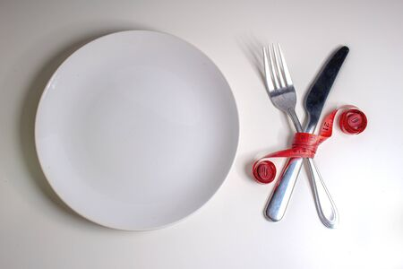 Losing weight. A fork and knife are wrapped in a red measuring tape next to a white plate with a white background