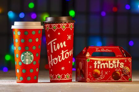 Calgary, Alberta, Canada. Jan 13, 2020. Christmas Starbucks and Tim Hortons coffee cups with some bite-sized fried-dough box with Christmas lights on the background. Imagens