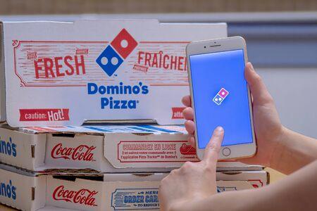 Calgary, Alberta. Canada Dec 26, 2019. Close up of a person using the Domino's Pizza application on an iPhone Plus. Domino's Pizza Domino's sticking to growth plan despite sales pressures. Illustrative Editorial