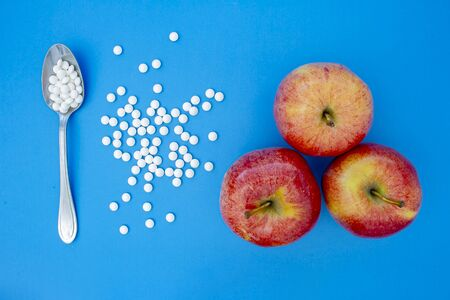 A spoon with supplements vitamins pills next to apples on a blue background