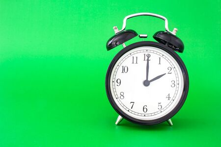 An isolated clock watch on a green background with a soft shadow 版權商用圖片