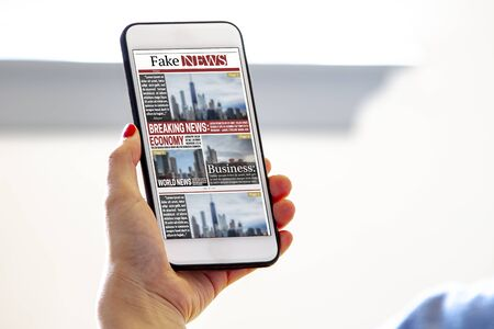 A female holding a smart phone reading fake news Banque d'images