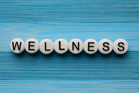 Wellness text on a blue wooden table