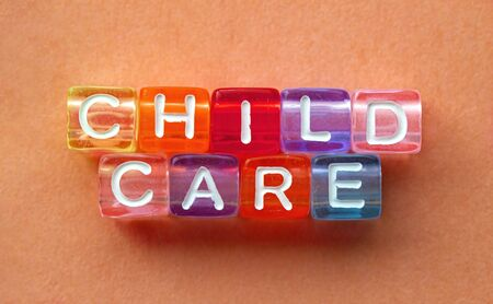 Child Care, message in text in colorful cubes on orange background Foto de archivo