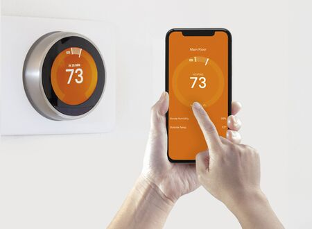 A person using a smart phone application warming up the room temperature with a wireless smart thermostat on a white background. Foto de archivo