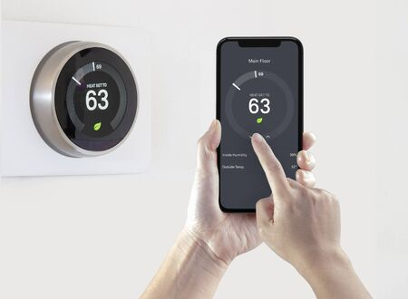 Eine Person, die eine Smartphone-Anwendung verwendet, die mit einem drahtlosen intelligenten Thermostat auf weißem Hintergrund Energie spart. Standard-Bild
