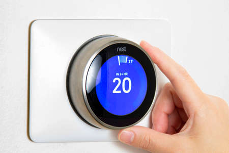 Calgary, Alberta, Canada. Jun 5, 2020. A person cooling down Home Air Conditioning, temperature is on centigrade celsius metrics using a Nest smart thermostat on a white wall. Editoriali