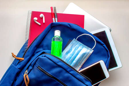 A blue school bag pack with sanitizer and a face mask, pencils earphones, tablet, computer and a smartphone. Back to school during global pandemic. Covid 19.