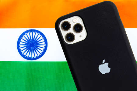 Calgary, Alberta, Canada. Oct 12, 2020. An India flag with an Apple iPhone Pro Max. Concept: Apple manufacturing products in india.