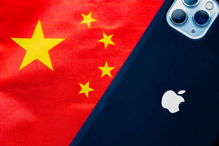 Calgary, Alberta, Canada. Oct 11, 2020. A China flag with an Apple iPhone Max Pro 11. Concept: Apple business relationship with China. Editorial