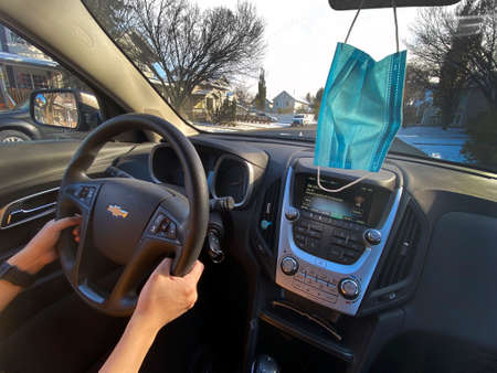 Calgary Alberta, Canada. Oct 17, 2020. A person driving a Chevrolet car on a sunny day, with a face mask hanging from the mirror. Cocept: Driving during Covid-19 pandemic Editorial