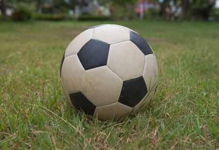 Traditional old soccer ball on green grass.football,
