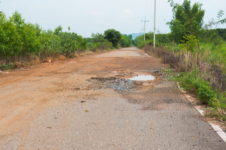pit fall: tarmac road in the countryside with potholes and puddles