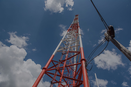 telecommunication tall tower, white and red and blue sky.