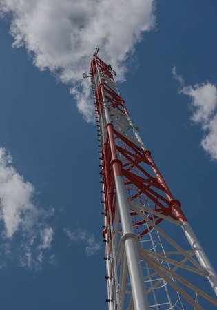 telephone poles: telecommunication tall tower, white and red and blue sky.