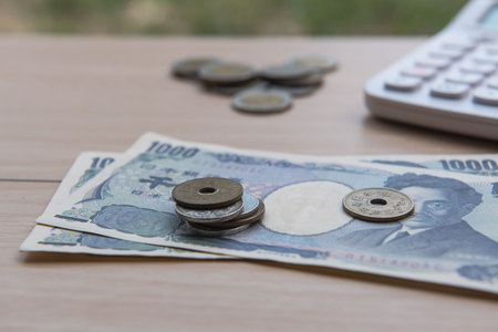 Closeup coin yen and banknotes Japanese and Calculator on wooden background. Currency of Japan. Stock Photo