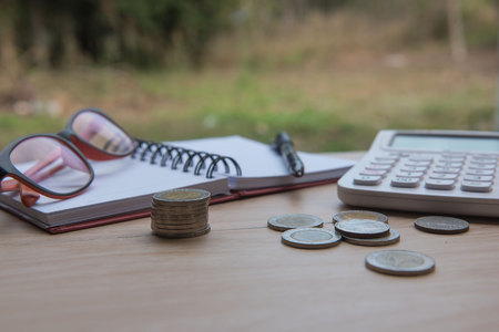 book concept: Business on financial report . Closeup coin and banknotes and Calculator , book on wooden background.