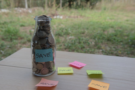 """""""Save"""" Writing in the paper, Coins in a glass jar, concept Saving Money  step with deposit coin in bank stack growing business."""