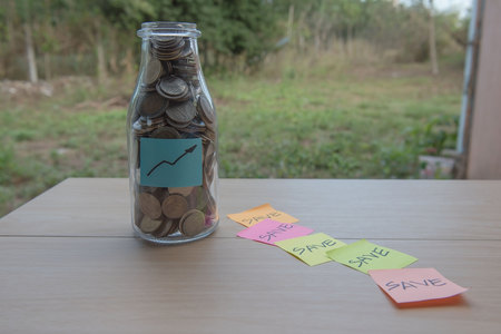graph Writing in the paper, Coins in a glass jar, concept Saving Money  step with deposit coin in bank stack growing business. Stock Photo
