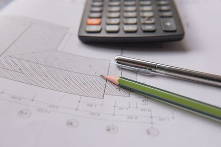 architect tools: pencil  pen and calculator on blueprints. Architectural and engineering housing concept.