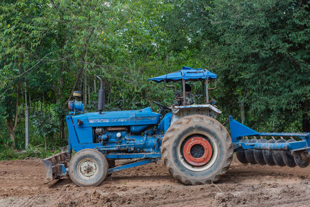 agricultural tenure: A tractor working in farm with  agricultural workers .