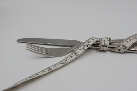 measuring tape with knife and fork isolated on white background , health concept .