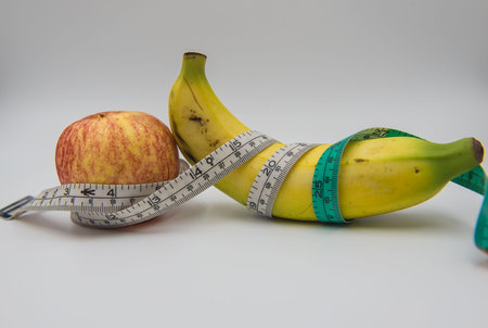 Yellow banana and red apple Measuring tape wrapped around on white background , health concept . Stock Photo