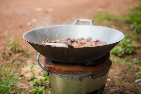 cooking with pan and charcoal stove .