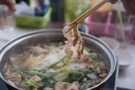 しゃぶしゃぶまたはすき焼き鍋、豚肉、箸を使用してレストランで日本食を持っている手。