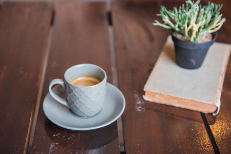 sooth: Cup coffee on White wooden table and old book and pot .