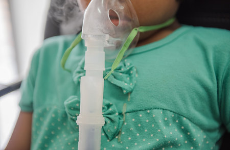 Young woman doing inhalation nebulizer with smoke from oxygen mask in the hospital. Reklamní fotografie
