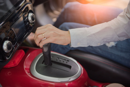 Closeup of hand on gear stick driving car. Stock Photo