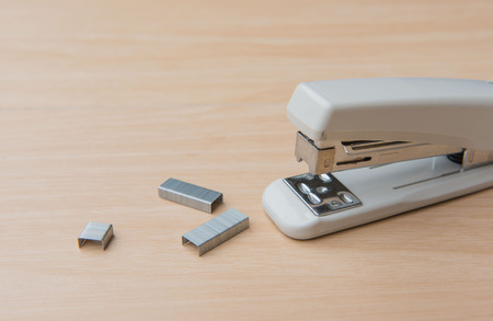 stapled: Stapler and staples on a wood background.