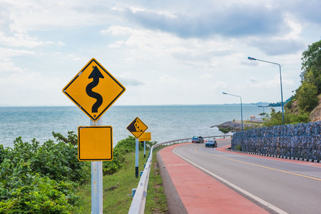 danger ahead: Yellow sign with winding road symbol in the countryside sea and sky background . Stock Photo
