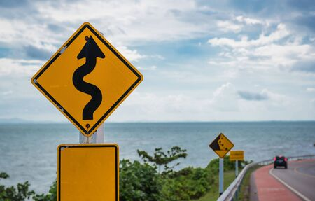 slip hazard: Yellow sign with winding road symbol in the countryside sea and sky background . Stock Photo