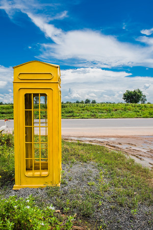 Yellow phone booth in countryside  and sky background .