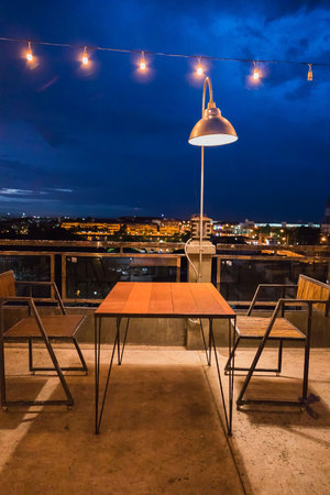 Wooden table and chair outdoor at night .