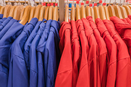 many t-shirts on the rack in shop for sale.