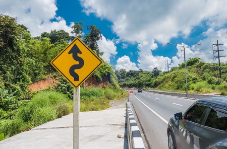 Yellow sign with winding road symbol in the countryside and sky background . Stock Photo