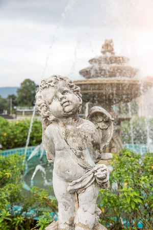 Cute little child sculpture decorate in front of fountain in the garden .