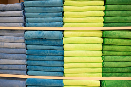 many colorful towels is folding in shelfs at store for Sales .