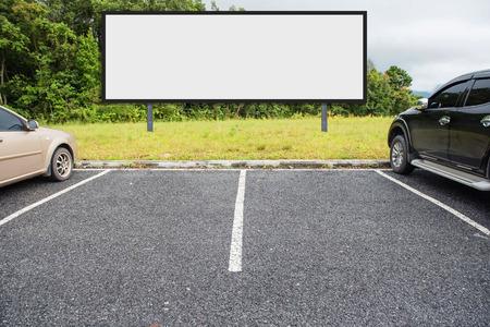Parkplatz im Freien und leere weiße Plakatwand. Leerzeichen für Text und Bilder. Standard-Bild