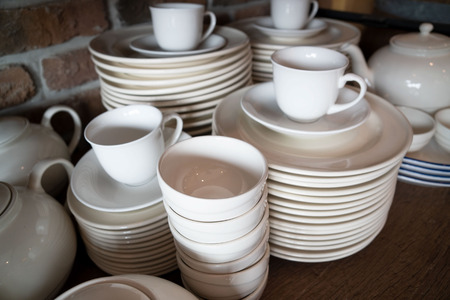 Many white plates are stacked together.a stack of white dish .