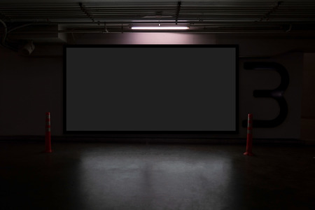 indoor car parking and empty black billboard .Blank space for text and images.
