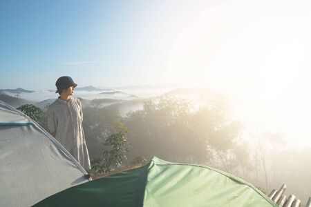 young woman standing for amazing landscape of blue sky and mountains in morning fog. Happy freedom for success and bliss concept. 写真素材