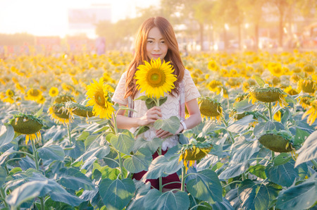 Cute asian girl in the field full of sunflowers sunlight. vintage tone, Selective focus on face. Imagens