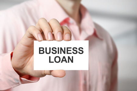 Business loan text on the card in hand man.