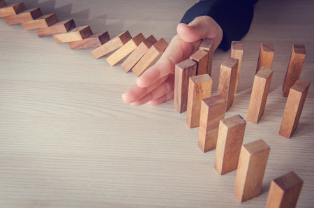 fragile economy: Businesswoman hand stopping the domino wooden effect concept for business. Risk.